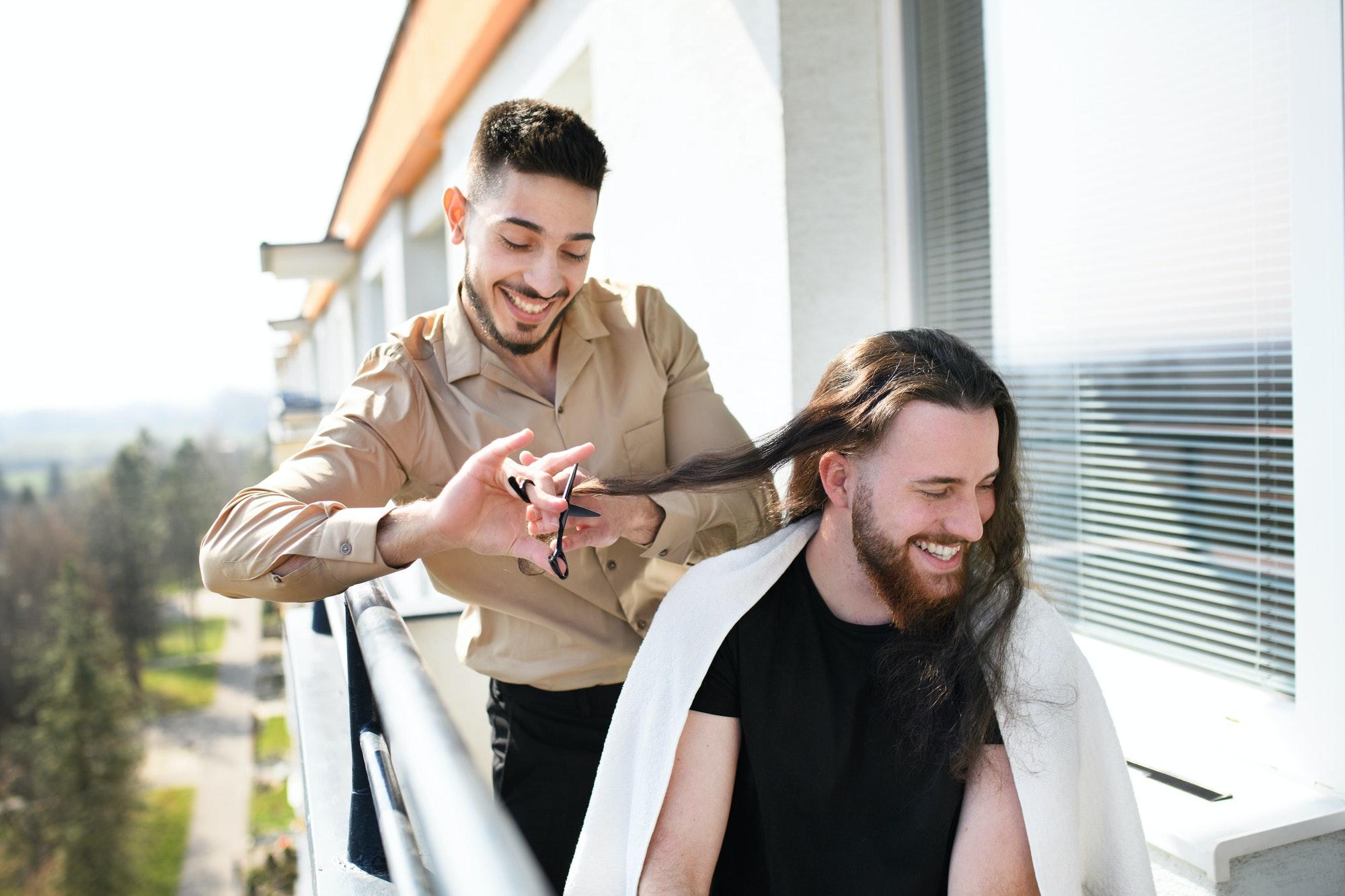 Haircut on balcony at home, coronavirus and lockdown concept