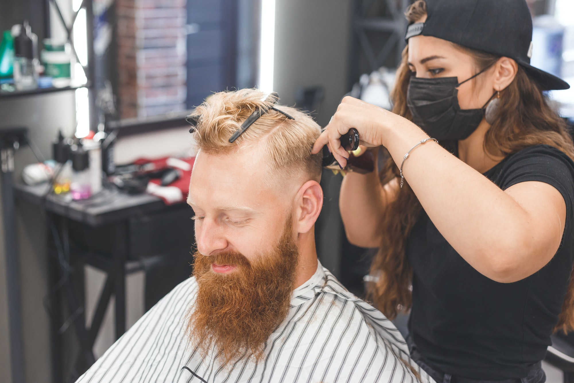 Woman barber making haircut to redhaired man with beard in barbershop