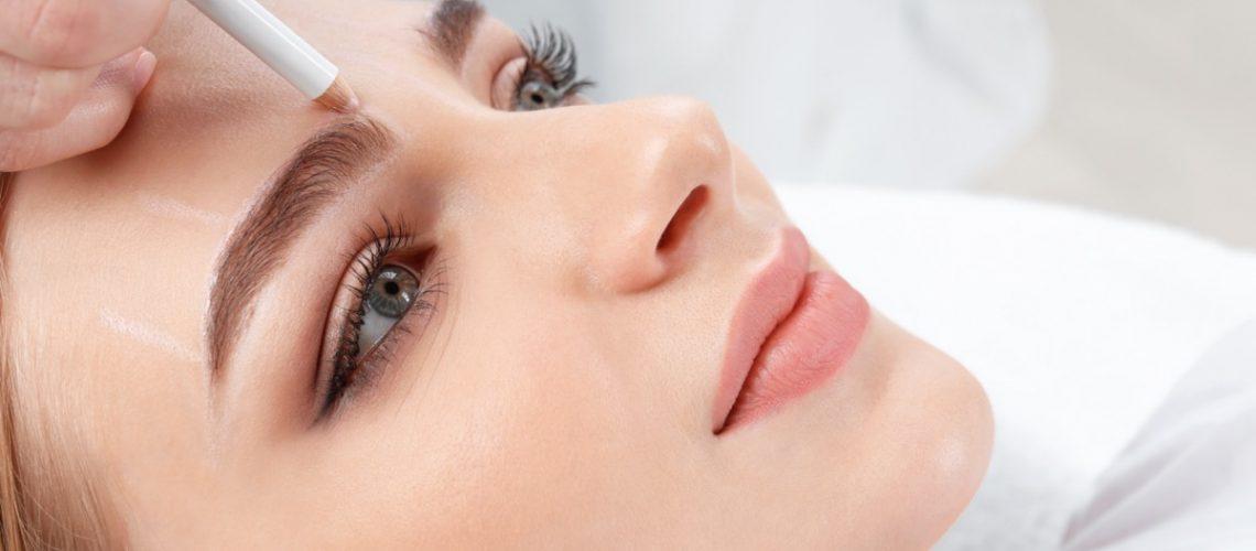 Cosmetologist preparing young woman for  eyebrow permanent makeup procedure, closeup