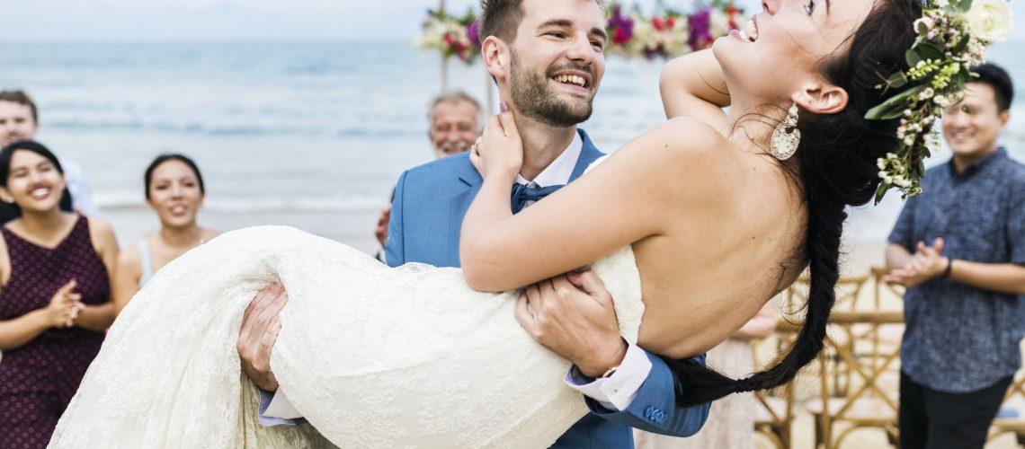 Cheerful newlyweds at beach wedding ceremony