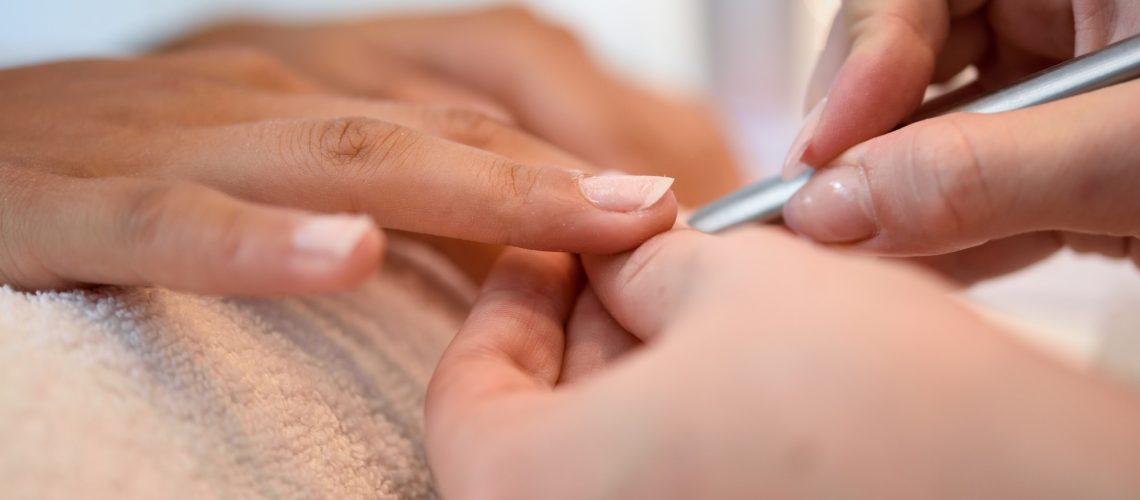 Woman in a nail salon receiving a manicure with nail file
